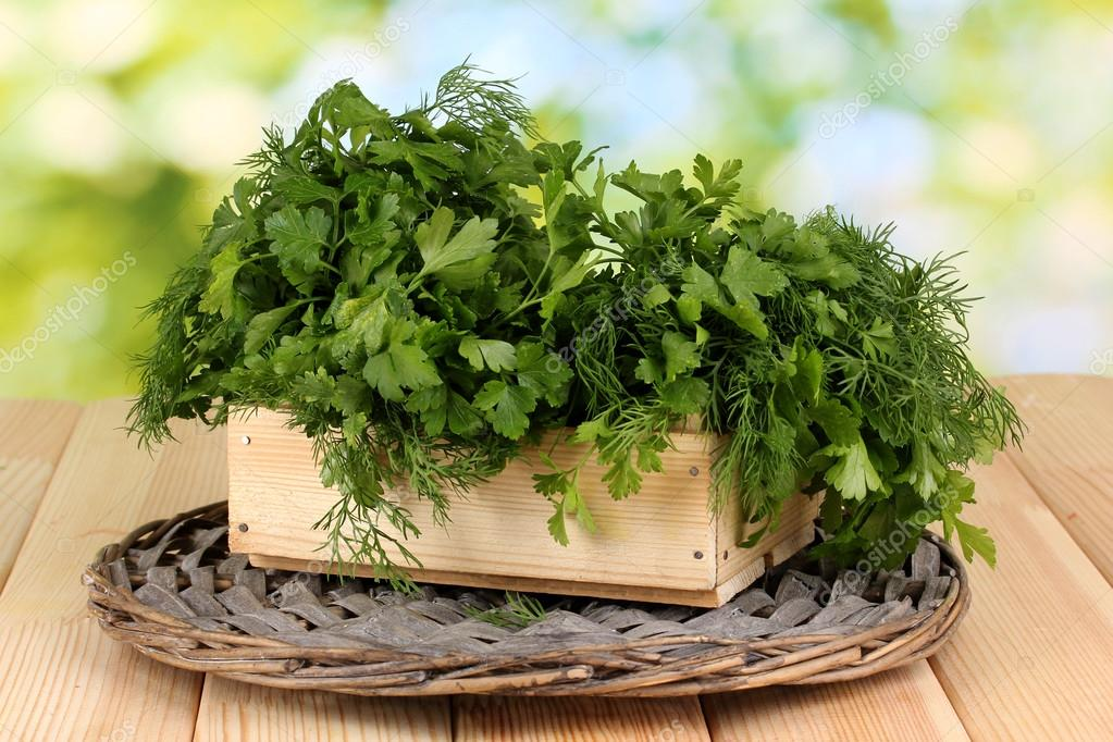 Wooden box with parsley and dill on wicker cradle on wooden table on natural background — Stock Photo #12872403