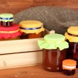 Stock Photo: Jars with canned fruit on wooden background