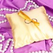 Wedding rings on satin pillow on purple cloth background - Foto Stock