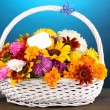 Royalty-Free Stock Photo: Beautiful bouquet of bright flowers in white basket on wooden table on blue