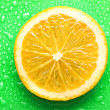 Slice of orange with drop on green background — Stock Photo #12889280