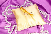 Wedding rings on satin pillow on purple cloth background — Stock Photo