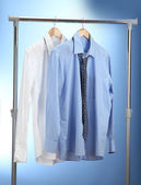 Blue and white shirts with tie on wooden hanger on blue background — Stock Photo