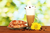 Glass of fresh coffee cocktail and saucer with bagels on bright green backg — Stock Photo