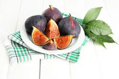 Ripe sweet figs with leaves on plate, on wooden table — Stock Photo