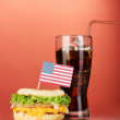 Tasty sandwich with american flag and cola, on red background — Stock Photo