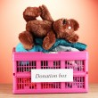 Donation box with clothing on red background close-up — ストック写真