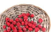 Raspberries on wicker mat isolated on white — Stock Photo