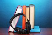 Fones de ouvido em livros sobre a mesa de madeira em fundo azul — Foto Stock
