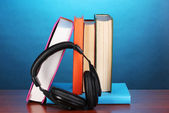 Headphones on books on wooden table on blue background — Stock fotografie