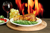 Roast chicken with french fries and cucumbers, glass of wine on wooden tabl — Stock Photo