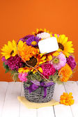 Beautiful bouquet of bright flowers with paper note on wooden table on oran — Stock Photo