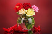 Beautiful roses in glass vase on red background — Stock Photo