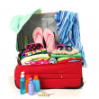 Red travel suitcase with personal belongings isolated on white — Stock Photo