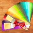 Paint brushes and bright palette of colors on wooden background - Stok fotoğraf