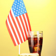 Tasty sandwich and cola with american flag, on yellow background — Stock Photo