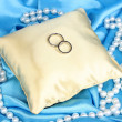 Wedding rings on satin pillow on blue cloth background — Stock Photo #13126064