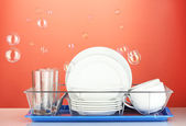 Clean dishes on stand on red background — Stock Photo