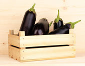 Fresh eggplants in crate on wooden background — Stock Photo