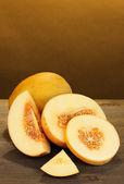 Couper les melons mûrs sur table en bois sur fond orange — Photo