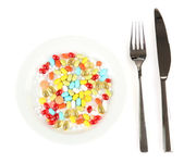 A lot of pills in a plate with knife and fork isolated on white — Stock Photo
