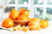 Tangerines with leaves in a beautiful basket, on wooden table on window bac — Stock Photo