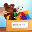 Donation box with children toys on blue background close-up — Stock Photo #13197181