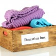 Donation box with clothing isolated on white — Stock Photo