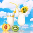 Delicious milk shake with fruit on table on sky background - Stock Photo