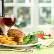 Roast chicken with french fries and cucumbers, glass of wine on green table - Stockfoto