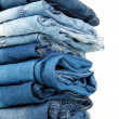 Lot of different blue jeans close-up isolated on white — Stock Photo