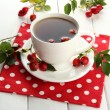 Cup of tea with hip roses, on wooden table - Stock fotografie