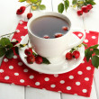 Cup of tea with hip roses, on wooden table - Stockfoto