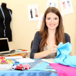 Beautiful young dressmaker in workroom - ストック写真