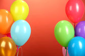 Colorful balloons on red background — Stock Photo