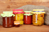Jars with canned fruit on wooden background — Stock Photo