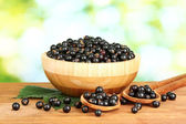Fresh black currant in wooden bowl on green background close-up — Stock Photo