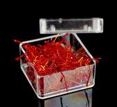 Stigmas of saffron in transparent bowl isolated on black background close-u — Stock Photo