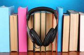 Auriculares en libros sobre tabla de madera sobre fondo azul — Foto de Stock