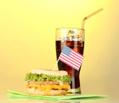 Tasty sandwich with american flag and cola, on yellow background — Stock Photo