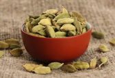 Cardamomo verde en un tazón ceramicos en primer plano de fondo de lona — Foto de Stock