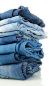 Lot of different blue jeans close-up isolated on white — Foto de Stock