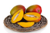 Ripe appetizing mango on wicker cradle isolated on white — Stock Photo
