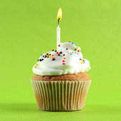 Tasty birthday cupcake with candle, on green background — Stock Photo
