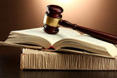 Wooden gavel on books, on brown background — Stock Photo