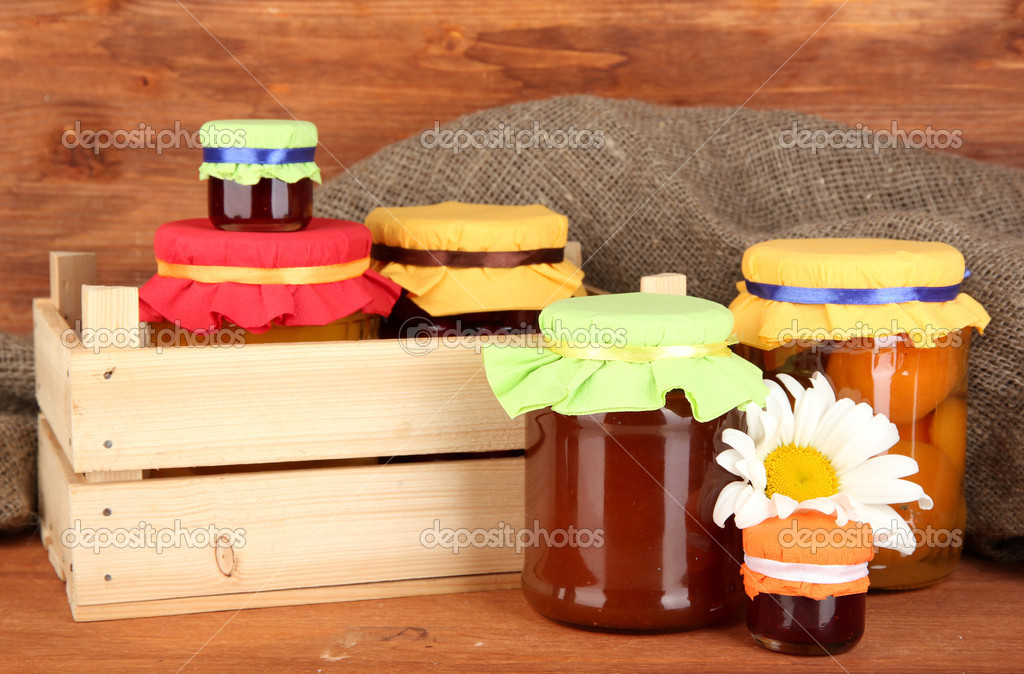 Jars with canned fruit on wooden background — Stock Photo #13196738