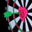 Stock Photo: Darts with stickers depicting life values close-up on black background