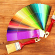 Paint brushes and bright palette of colors on wooden background - ストック写真