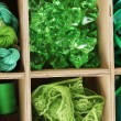 Green thread and material for handicrafts in box close-up — Stock Photo #13206085