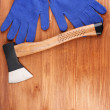 Axe and gloves on wooden background - Stock Photo